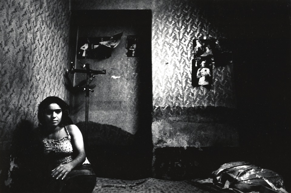 Woman sitting on bed in room with posters, photo from Kaveh Golestan's Prostitute series, 1975-77